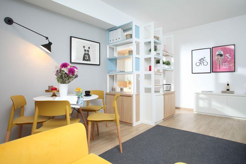 O organizare foarte inspirată a spațiului din living a permis conturarea unei mici zone-dining, cu masă rotundă de la Domicilio și scaune de la ioooi.ro, valorificarea spațiului de sub grindă prin plasarea unei etajere multifuncționale, realizată la comandă prin Delta Studio, și conturarea unui loc de relaxare format din canapeaua albă de la IKEA și fotoliul galben de la MaisonDeco. Foto: Sorin Iacob